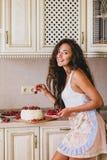 做蛋糕的年轻美丽的妇女在厨房 图库摄影