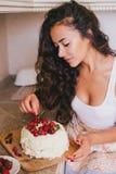 做蛋糕的年轻美丽的妇女在厨房 库存图片