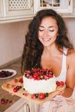 做蛋糕的年轻美丽的妇女在厨房 免版税图库摄影