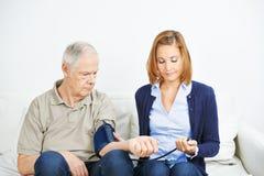 做血压测量的护理服务 免版税库存照片