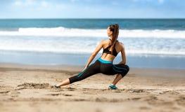 做行使在沙子海岸的运动的妇女 库存图片