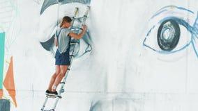 做街道画的美丽的女孩与烟雾剂喷射的大女性面孔在都市街道墙壁 站立在梯子的她 股票视频