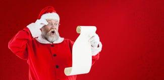 做表情的圣诞老人的综合图象,当读纸卷时 免版税库存照片