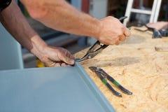 做裁减的盖屋顶的人在金属板 库存照片