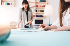 做设计师服装的两名妇女裁缝在陈列室里 工作在缝合的年轻女性专业裁缝 库存照片