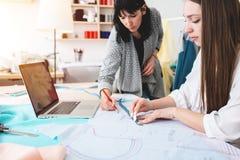 做设计师服装的两名妇女裁缝在陈列室里 工作在缝合的年轻女性专业裁缝 免版税图库摄影