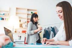 做设计师服装的两名妇女裁缝在陈列室里 工作在缝合的年轻女性专业裁缝 免版税库存图片