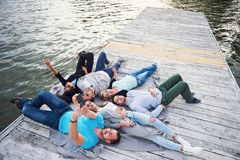 做说谎在码头、女孩最好的朋友和男孩的Selfies高兴地的小组美丽的青年人 免版税库存照片