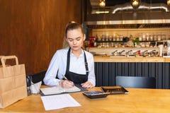 做财务的小家庭餐馆老板计算小企业票据和费用  库存图片