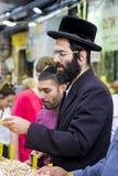 做购买的一个正统Chassidic犹太人由一个摊位在Mahane耶胡达街市上在耶路撒冷以色列 免版税库存照片