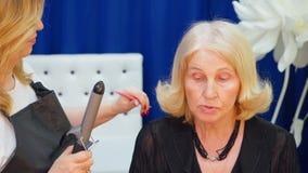 做资深妇女的发式专家卷曲发型发廊的 卷曲年长妇女的金发的美发师与 股票视频