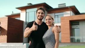 做赞许姿态的愉快的夫妇在豪华房子附近 股票录像
