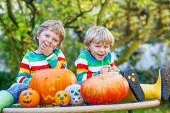 做起重器o灯笼的两个小双男孩为在autu的万圣夜 免版税库存照片