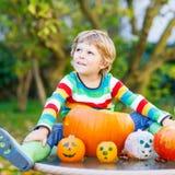做起重器o灯笼的小孩男孩为在秋天雀鳝的万圣夜 免版税库存图片