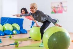 做起重机的适合的白种人妇女行使在一条腿的身分有他们的胳膊的对坚持平衡球的边 库存图片