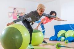 做起重机的适合的白种人妇女行使在一条腿的身分有他们的胳膊的对坚持平衡球的边 免版税库存图片