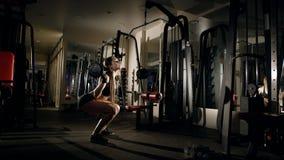做蹲与在健身房的杠铃的女孩 免版税库存照片