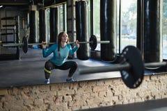 做蹲坐的健身房的肌肉妇女 免版税库存照片
