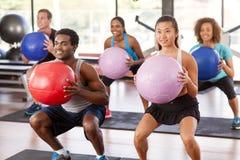 做蹲坐的健身房类 免版税图库摄影