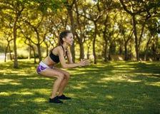 做蹲坐的女孩实践的体育在公园 免版税库存照片
