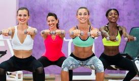 做蹲坐的妇女举行哑铃在功能训练grou 免版税库存照片