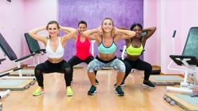 做蹲坐的妇女在锻炼在现代健康c的小组类期间 库存图片
