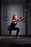 做蹲坐的年轻美丽的运动的妇女对在十字架适合的健身房的砖墙 免版税库存图片