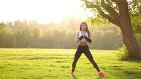 做蹲坐的年轻肌肉健身妇女在自然行使 影视素材