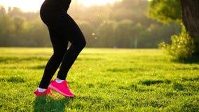 做蹲坐的年轻肌肉健身妇女在自然行使 股票录像