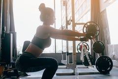 做蹲坐的运动服的年轻亚裔妇女在荒地室内健身房 免版税库存照片
