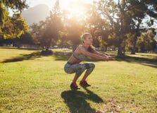做蹲的适合的少妇在公园 免版税库存照片