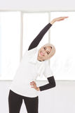 做身体和手舒展的回教运动的妇女 免版税库存照片