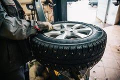 做轮胎替换和轮子的汽车修理师工作者平衡用在修理服务站的特别设备 库存图片