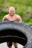 做轮胎轻碰锻炼的男性运动员 免版税库存照片