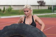 做轮胎轻碰锻炼的年轻人室外 库存图片