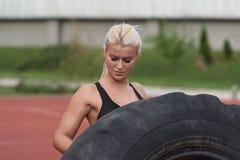做轮胎轻碰锻炼的年轻人室外 图库摄影