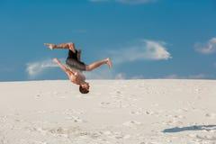 做轻碰或翻筋斗在沙子的年轻parkour人画象  免版税库存照片