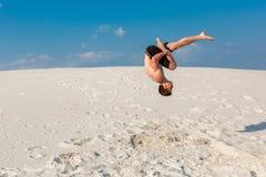 做轻碰或翻筋斗在沙子的年轻parkour人画象  库存图片