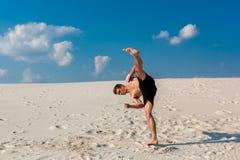 做轻碰或翻筋斗在沙子的年轻parkour人画象  免版税图库摄影