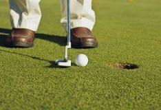 做轻轻一击的高尔夫球运动员 库存图片