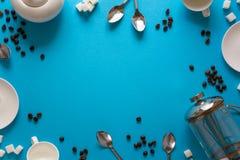 做辅助部件的各种各样的咖啡:法国咖啡新闻、杯子、茶碟、咖啡豆、匙子和糖在蓝纸背景 免版税库存照片