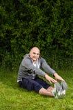 做运动的人舒展在绿色草甸的锻炼 免版税库存图片