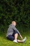 做运动的人舒展在绿色草甸的锻炼 免版税库存照片