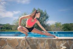做运动的妇女舒展锻炼在游泳池附近 免版税库存照片