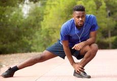 做适合的年轻非裔美国人的人舒展锻炼,当听到与耳机时的音乐 免版税库存照片