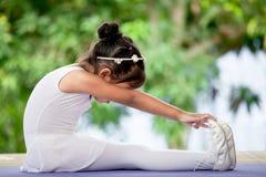 做逗人喜爱的亚裔儿童的女孩舒展锻炼 库存照片