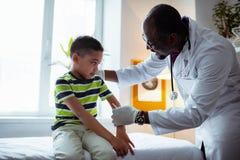 做逗人喜爱的小男孩的宜人的儿科医生射入 免版税库存照片