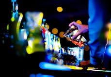 做酒精鸡尾酒的侍酒者在酒吧柜台在夜总会,男服务员做鸡尾酒 免版税库存图片
