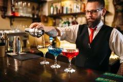 做酒精鸡尾酒的男服务员在夜总会 库存图片