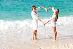 做重点的新愉快的夫妇塑造在海滩。 免版税图库摄影